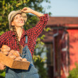 Woman farmer carrying crate with freshly harvested vegetables in garden — Stock Photo