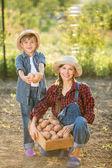 Mother and son harvesting on allotment — Stock Photo