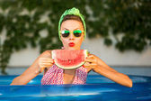Beauty model with watermelon in swimming pool — Stock Photo