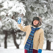 Winter - cute boy have fun with snow in winter park — Stock Photo