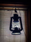 Silhouette of a kerosene lantern in the window — Stock Photo
