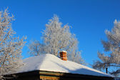 Snowy roof with brick chimney — Stock Photo