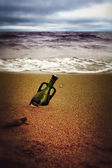 Bottle with a note in the sand on the shore — Stock Photo