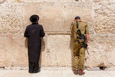 Soldier and orthodox jewish man pray at the western wall, Jerusalem — Stock Photo