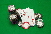 Cards showing pair of aces with chips on green background — Stock Photo