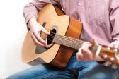 Shot of man in shirt and jeans playing on classic guitar — Stock Photo