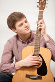 Portrait of young handsome man playing on acoustic guitar — Stock Photo