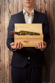Elegant man holding box with wine against wooden background — Stock Photo