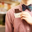 Man taking chocolate out of pocket at street — Stock Photo