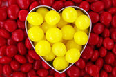 Heart with yellow and red candy — Stock fotografie
