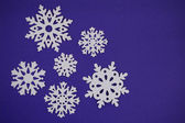 Snowflake cut outs on blue purple background — Stockfoto
