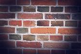 Väderbitna färgade gammal tegel vägg bakgrund — Stockfoto