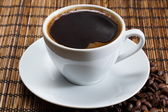 Natural black coffee in a white cup — Stock Photo