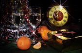 Christmas still life with wine, tangerines and hours — Stock Photo