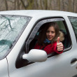 Young woman looking out of car and showing success — Stock Photo
