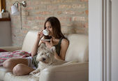 Girl drinks coffee and relax with dog — Stock Photo