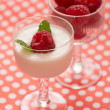 Raspberry dessert with yogurt in a glass and dotted table — Stock Photo #45729225