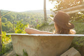 Sexy cowgirl sitting in bath on ranch — Stock Photo