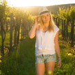 Beautiful girl standing in hat between grapes. — Stock Photo