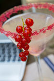 Working at home with currants cocktail and laptop — Stock Photo