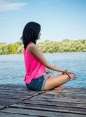 Woman doing yoga exercises on the beach — Stock Photo