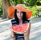 Beautiful girl eating fresh watermelon in big hat — Stock Photo