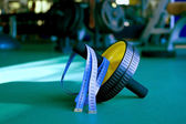 Exercise wheel and tape measuring in gym — Stock Photo