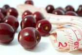 Fruit diet. Cherries with measuring tape on white background — Foto de Stock