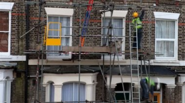 Construction workers setting up scaffold — Wideo stockowe