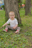 Young adorable cheerful baby sit in park on green grass and play — Stock Photo