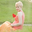 Pregnant woman enjoying summer park holding a paper red heart, o — Stock Photo #42875091