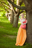 Young happy pregnant woman relaxing in nature — Stockfoto