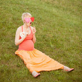 Pregnant woman enjoying summer park holding a paper red heart, o — Stock Photo
