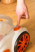 Closeup of a hand to turn on the vacuum cleaner. Man is unrecogn — Stock Photo