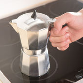 Italian coffee pot in hand on a black electric cooker. — Stock Photo