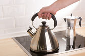 Tea kettle in hand on black stove — Stock Photo