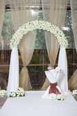 Beautiful wedding arch with roses in the restaurant — Stock Photo