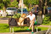 man with dog on bench in park. — Stock Photo