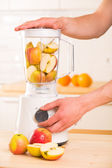 White blender with apples on a wooden table. — Stock Photo