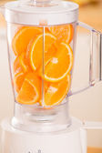 White blender with juicy oranges on a wooden table — Stock Photo