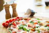 Pizza with cherry tomatoes, prosciutto and ruccola — Stock Photo