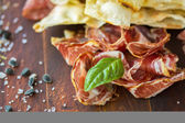 Homemade prosciutto and basil on a wooden board — Stock Photo