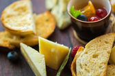 Assorted cheese on a wooden board. — Stock Photo