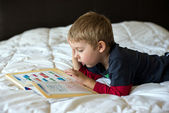 A young blonde boy is learning on a bed — Foto Stock