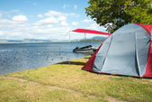 Tent on a camping site near a lake — Stock Photo