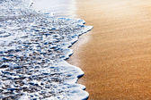 Waves splashing on sandy beach — Stock Photo