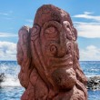 Red carving of a face on a moai at seashore — Stock Photo