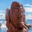 Red carving of a face on a moai at seashore — Stock Photo #39588907