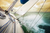 Sailing fast with water splashing on deck under dramatic sky — ストック写真