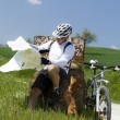 Cyclist on green countryside wit his dog — Stock Photo
